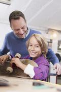 Stock Photo of Germany, Leipzig, Father and son repairing skateboard
