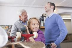 Germany, Leipzig, Grandfather, father and son repairing skateboard Stock Photos