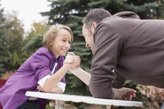 Germany, Leipzig, Father and son arm wrestling, smiling Stock Photos