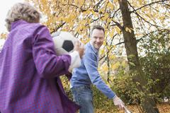 Stock Photo of Germany, Leipzig, Boy holding football, father collecting leaves