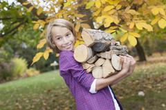 Germany, Leipzig, Boy holding firewood, smiling Stock Photos