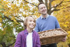 Stock Photo of Germany, Leipzig, Father and son collecting walnuts