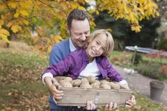 Stock Photo of Germany, Leipzig, Father and son collecting potatoes