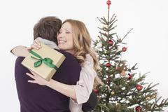 Couple embracing with gift in hand, smiling Stock Photos