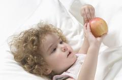 Girl lying on bed with apple - stock photo
