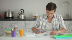 Good-looking guy sitting at table with books and studying Stock Footage