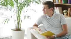 Good-looking young man on sofa reading book and smiling Stock Footage
