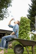 Germany, Hamburg, Man sitting on wheelbarrow and drinking water in allotment - stock photo