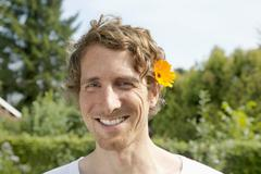 Germany, Hamburg, Man wearing marigold in allotment garden Stock Photos