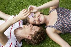Germany, Hamburg, Man and woman lying on grass in allotment garden - stock photo