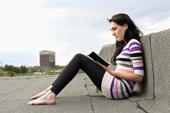 Stock Photo of Germany, Hamburg, Young woman sitting on roof and reading book