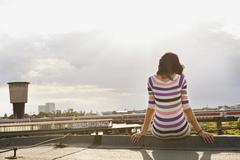 Stock Photo of Germany, Hamburg, Young woman sitting at edge of roof