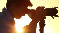 Camera on tripod, young cameraman shoots photos and videos, dusk, click for HD - stock footage
