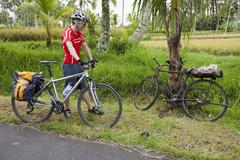 Indonesia, Bali, Tampaksiring, Man with bicycle standing by rural road Stock Photos