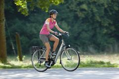Stock Photo of Germany, Bavaria, Munich, Mid adult woman riding electric bicycle