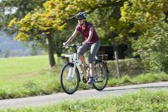 Germany, Bavaria, Mid adult woman riding electric bicycle Stock Photos
