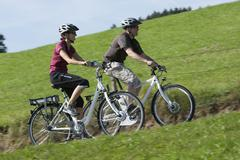 Stock Photo of Germany, Bavaria, Man and woman riding electric bicycle