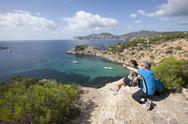 Stock Photo of Spain, Ibiza, Porroig, Mature man and mid adult woman looking at view