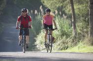 Stock Photo of Spain, Ibiza, Mature man and mid adult woman riding bicycle