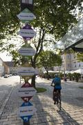 Austria, Styria, Bad Radkersburg, Mature man riding bicycle with street name - stock photo