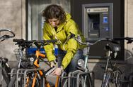 Stock Photo of Germany, Bavaria, Munich, Mid adult woman locking bicycle