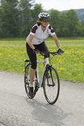 Germany, Bavaria, Mid adult woman riding bicycle - stock photo