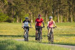 Germany, Bavaria, Man and women riding bicycle - stock photo