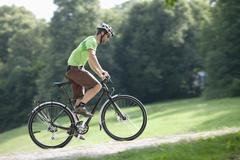 Stock Photo of Germany, Bavaria, Munich, Young man cycling through single track