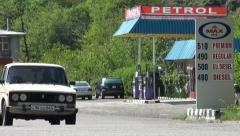 Old Lada drives past petrol station in Armenia Stock Footage