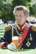 Stock Photo of Germany, Man as King Ludwig of Bavaria with beer mug, smiling