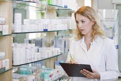 Germany, Brandenburg, Pharmacist checking products in pharmacy Stock Photos