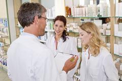 Germany, Brandenburg, Man and women having team meeting in pharmacy Stock Photos
