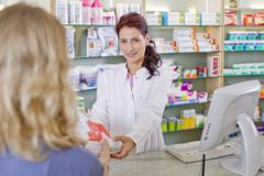 Germany, Brandenburg, Pharmacist handing medicne to woman - stock photo