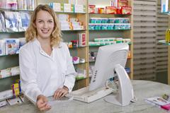 Germany, Brandenburg, Pharmacist holding prescription, smiling, portrait - stock photo