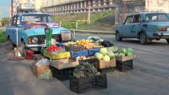 Old Lada drives past classic fruit stall in Armenia Stock Footage