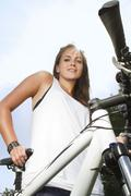 Stock Photo of Germany, Berlin, Young woman with her bicycle, smiling, portrait