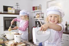 Stock Photo of Germany, Girls making dough in kitchem