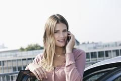 Germany, Cologne, Young woman on phone near parking lot, smiling, portrait - stock photo