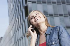 Germany, Cologne, Young woman on phone, smiling, portrait Stock Photos