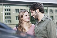 Germany, Cologne, Young couple near car, smiling - stock photo