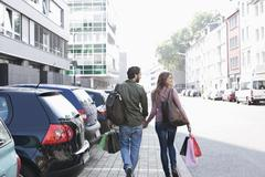 Germany, Cologne, Young couple with shopping bags near parking lot, smiling - stock photo