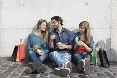 Germany, Cologne, Young man and woman with ice cream and shopping bags, smiling - stock photo