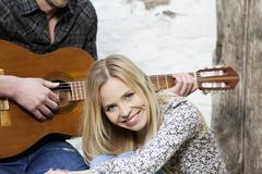 Woman smiling, man playing guitar in background Stock Photos