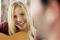 Woman plucking guitar, smiling, close up - stock photo