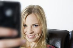 Young woman photographing, smiling, portrait - stock photo