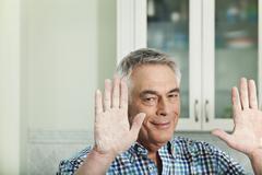 Germany, Berlin, Senior man showing handful of flour, portrait - stock photo