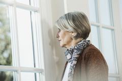 Germany, Berlin, Senior woman looking through window Stock Photos