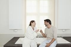 Germany, Berlin, Mature couple sitting on bathtub with sparkling wine Stock Photos