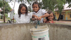 Cambodia School girls retrieving rain water from well - stock footage