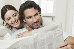 Stock Photo of Germany, Berlin, Mature couple reading newspaper, smiling